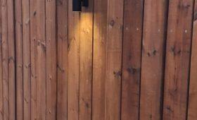 Habillage bois d'un mur avec des lames de terrasse brunes et intégration de 4 lampes design