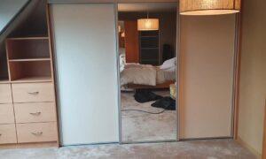 Fabrication et pose d'un placard sous pente, avec penderie et étagères, façade coulissante et élément avec tiroirs.